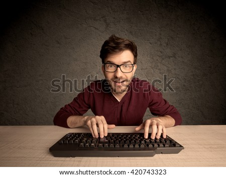 A young hacker with glasses dressed in casual clothes sitting at a desk and working on a computer keyboard in front of black clear concrete wall background concept - stock photo