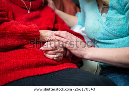 A young hand holding an elderly pair of hands - stock photo