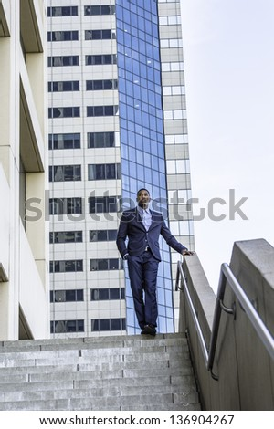 A young handsome black businessman is standing outside of a business building and confidently looking forward./Portrait of Young Black Businessman - stock photo