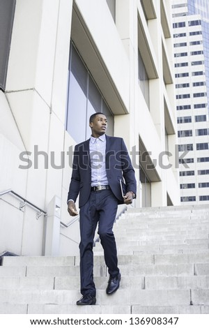 A young handsome black businessman is walking down on steps from a business building. - stock photo