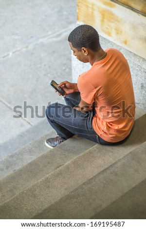 A young handsome black guy is sitting on stairs on the corner, checking messages on his mobile phone. / Text Anywhere - stock photo