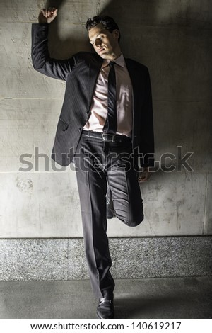 A young handsome businessman is stressfully leaning on a wall and thinking./Stressful - stock photo