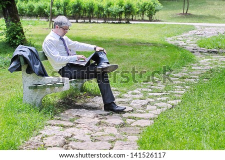 A young handsome businessman using laptop sitting on a bench in a park... looking and smiling into camera./Businessman using laptop sitting on a bench - stock photo