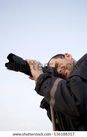 A young handsome photographer with a professional camera, no trademarks visible - stock photo