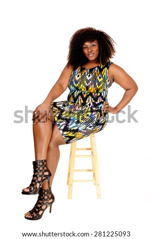 A young happy African American woman sitting on a chair, smiling,isolated for white background. - stock photo