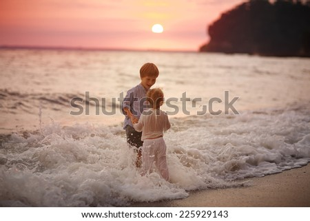 A young happy boy and his little cute sister walking on the sea shore on a warm summer evening. Friendship between siblings.  - stock photo