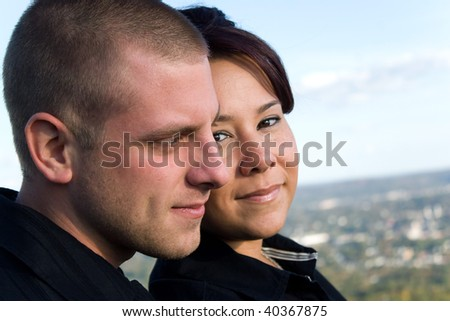 A young happy couple enjoying the scenic view outdoors. - stock photo