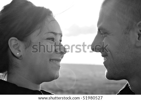 A young happy couple gazing into each others eyes outdoors on a sunny day.  Intentional lens flare. - stock photo