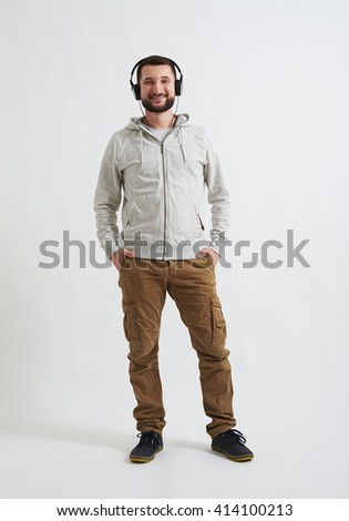 A young happy man in casual clothes with headphones on his head is listening music - stock photo