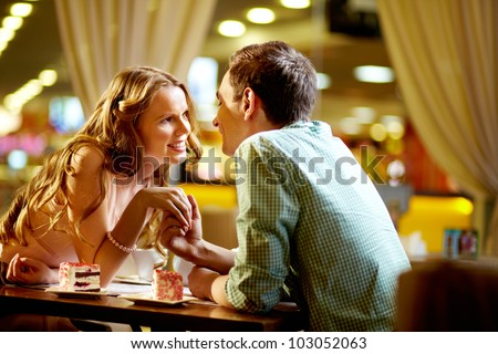 A young happy woman and her boyfriend looking at one another in restaurant - stock photo
