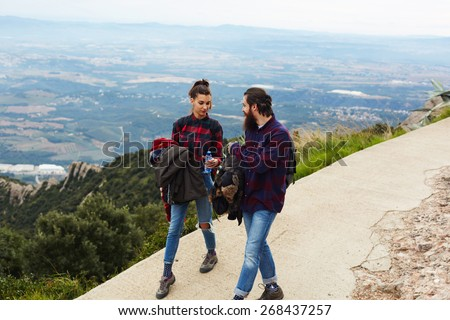 A young hiker woman giving the bottle of water to her friend, couple walking on the trail with beautiful horizon view from altitude - stock photo