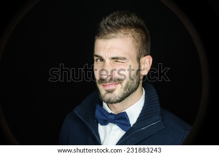 A young hipster man winking at the camera - stock photo