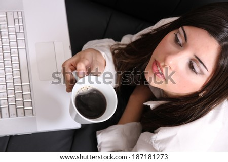 A young, hispanic adult girl watching a Laptop while drinking coffee. - stock photo
