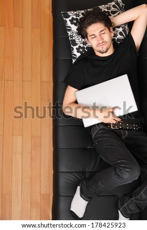 A young hispanic man with a laptop on the Sofa. - stock photo
