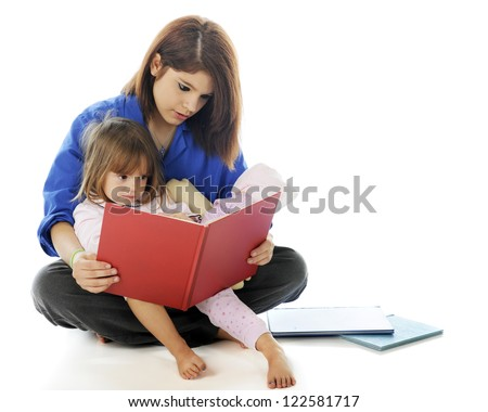 A young hospital volunteer and preschooler reading a book together.  On a white background. - stock photo