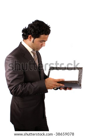 A young Indian businessman reading documents from a file, on white studio background. - stock photo