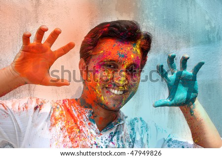 A young Indian guy having fun in Holi festival. - stock photo