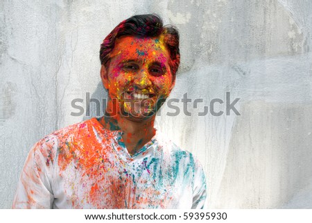 A young Indian guy traditionally covered with colorful holi festival powder. - stock photo
