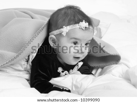 A young infant looking out from under a blanket. - stock photo