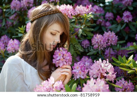 A young lady enjoys the smell of a rhododendron  blossom - stock photo