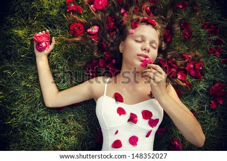 a young lady lies on the grass with roses - stock photo
