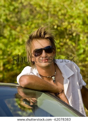 a young loose boy leans against the car - stock photo