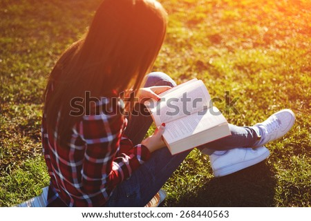 A young lovely woman relax reading an absorbing novel in beautiful the park - stock photo