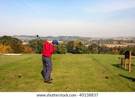 A young male golfer teeing off on an autumn morning on a golf course in England. Slight motion blur on the clubhead. Tee shot heading straight down the fairway. - stock photo