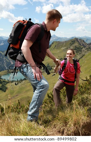 A young male hiker is helping a female hiker to climb a mountain in the German Alps near Oberstdorf. - stock photo
