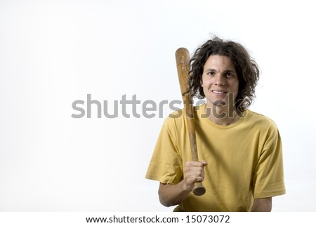 A young male holding a baseball bat to his shoulder.  He is smiling and looking at the camera. Horizontally framed shot. - stock photo