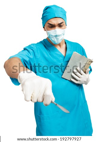 a young  male medical student (nurse, intern, doctor) with a scalpel and a book - stock photo