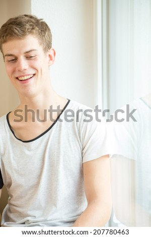A young male model is laughing in a bright, modern environment - stock photo