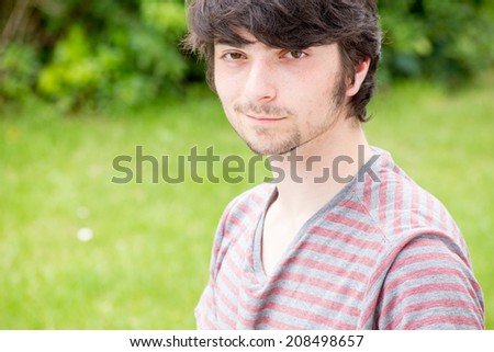 A young male model is looking into the camera  and seems very determined and confident - stock photo