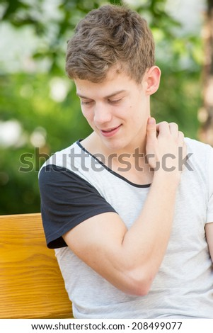 A young male model is reaching for his back with closed eyes in an attractive fashion - stock photo