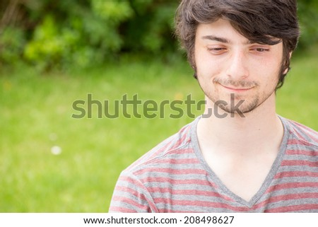 A young male model is smiling down with a silent grin on his face - stock photo