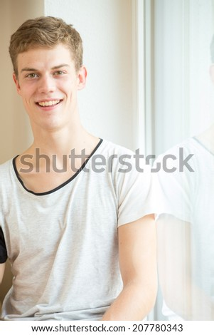 A young male model is smiling into the camera in a bright, modern environment - stock photo