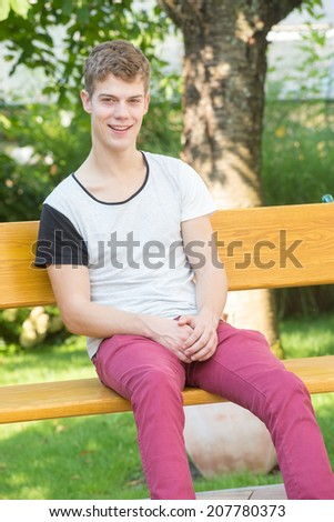 A young male model is smiling silently at the camera and sitting relaxedly on a beautiful wooden bench in a green garden - stock photo