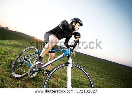 A young male riding a mountain bike outdoor at sunset. - stock photo
