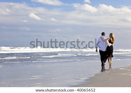 A young man and woman arms around each other walking as a romantic couple on a beach - stock photo