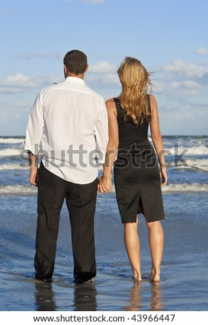 A young man and woman celebrating arms raised and holding hands as a romantic couple on a beach with a bright blue sky - stock photo