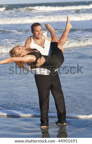 A young man and woman couple having romantic fun in the sea on a warm sunny beach - stock photo