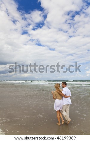 A young man and woman couple having romantic walk on a beach - stock photo