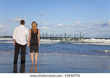A young man and woman holding hands as a romantic couple looking out to sea on a beach with a bright blue sky - stock photo