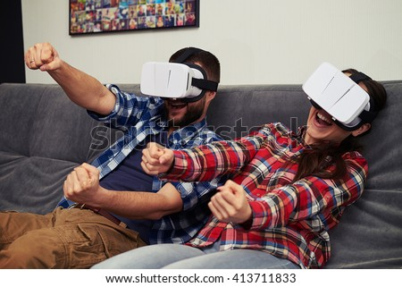 A young man and woman in casual clothes playing racing game using virtual reality headset - stock photo