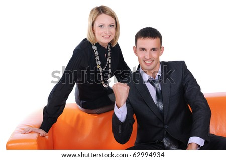 A young man and woman on the orange sofa working at a laptop - stock photo