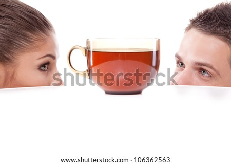 A young man and woman peeking from under the table at a large cup of tea - stock photo
