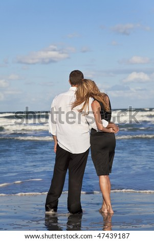 A young man and woman romantic couple in love arms around each other cuddling on a beach with a bright blue sky - stock photo
