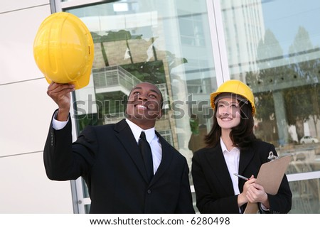 A young man and woman working as  architects on a building site - stock photo