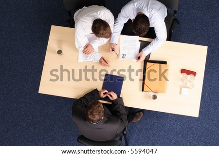 A young man at a a job interview with two interviewers, showing them his resume.Aerial shot taken from directly above the table. - stock photo