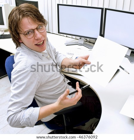 A young man behind a desk in an office, turning around to ask for help, holding a blank piece of paper for your message - stock photo